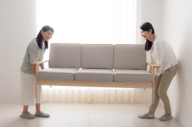 ソファを運ぶ女性