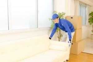 ソファを持ち上げる男性